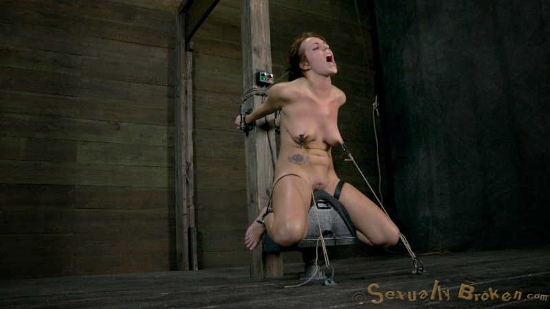 Restrained redhead sitting on a sybian and getting her throat fucked
